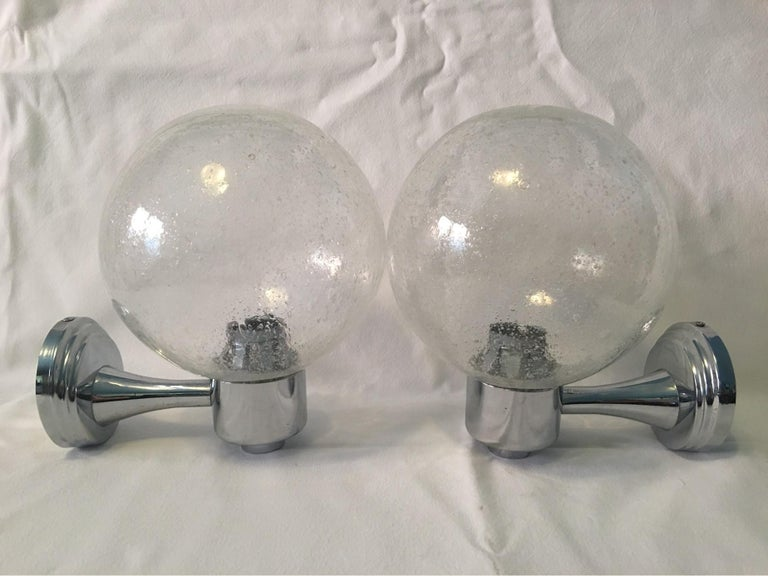 A pair of pretty Chrome and Air Bubble Glass Ball Sconces from the 1970s. When lit they create a lovely glass reflection through the Bubble Glass scheme. E#ach one requires one European E14 Candelabra Bulb up to 40 watts. The wall fixture
