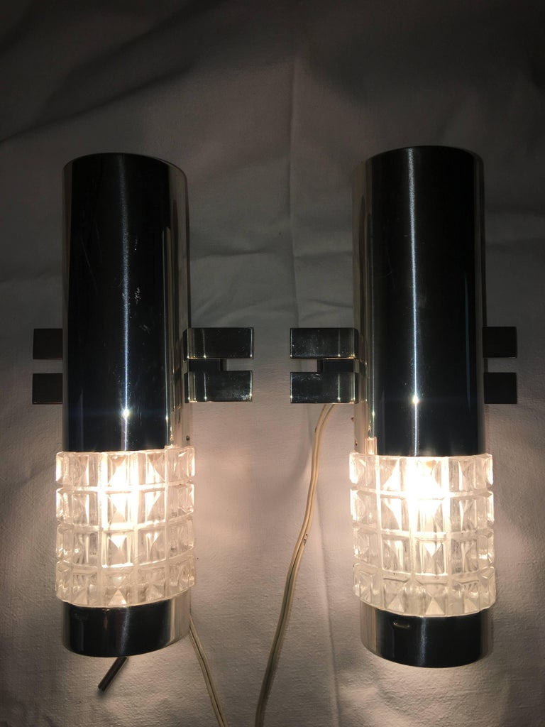 From Kaiser Leuchten of Germany. A pair of great looking 1960s chrome and glass Kaiser sconces. Equipped with on/off switch. Each requires one European E14 candelabra bulb max 40 W. Item will be shipped directly from Germany to buyer.