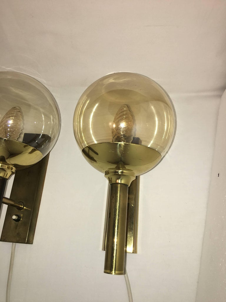 A pair of brass and smoke glass sconces designed by Svend Mejlstrom. Manufactured by Mejlstrom Belysning of Norway. The sconces have a very nice Patina and a 20 inch long cable. Each fixture requires one European E14 candelabra bulb up to 40 watts.