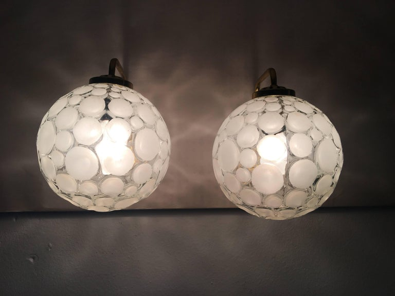 A pair of lovely 1960s French sconces made of brass with crater texture glass shades. Each of the two fixture requires one European style E14 candelabra bulb, up to 40 watts for maximum lighting enjoyment.