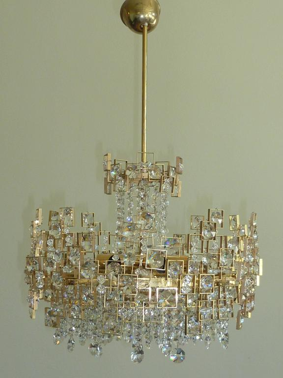"Gorgeous crystal chandelier by Lobmeyr. Large individual ""jewels"" and hundreds of individual crystals intricately placed among floating geometric brass frame with strings of cut crystals hanging on the bottom and the top. It requires"