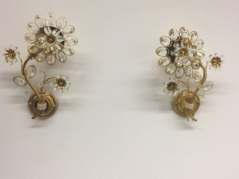 Pair of vintage gold-plated sconces with faceted crystal flowers made by the German company Palwa. Each fixture has one European style E14 socket. It requires one European E14 candelabra bulb.