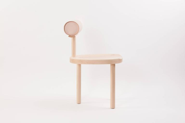 The UNA chair intersects the round wooden seat and legs with a leather upholstered cylindrical back. Using these fluid shapes allows greater focus on the details of the wood grain and pristinely stitched leather top.   Made of solid hard maple, with