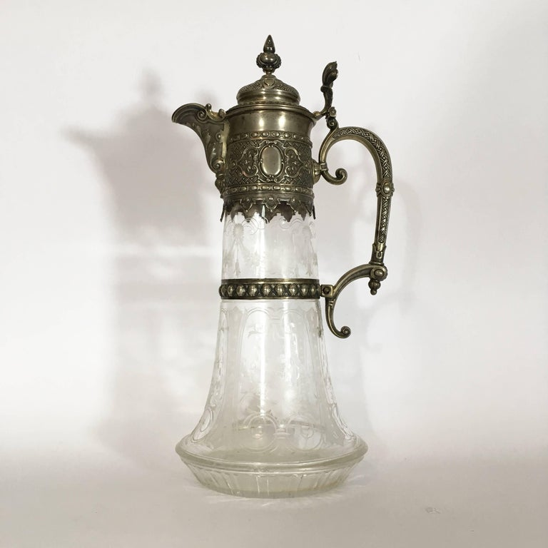 A stunning engraved glass decanter or carafe with gorgeous silver mountings transition style from Historicism towards Art Nouveau period. The decanter is made of glass, presents an elegant engraved decoration and is partially covered with beautiful