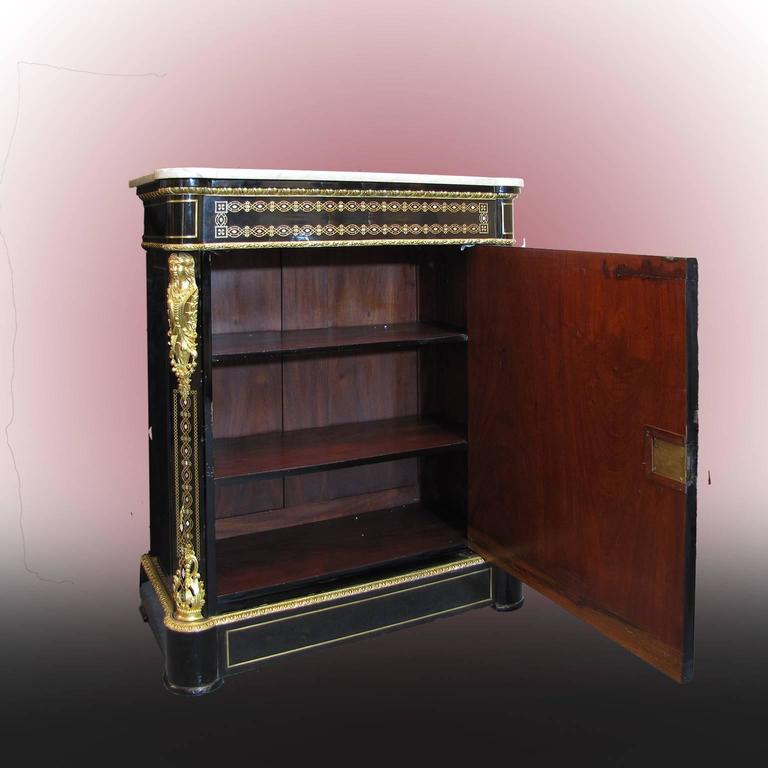 A beautiful French mid-19th century Napoleon III Credenza or sideboard in ebonized pear wood. This magnificent piece of furniture has got one single door, two shelves on the inside and it is surmounted by an elegant white marble top. The Credenza is