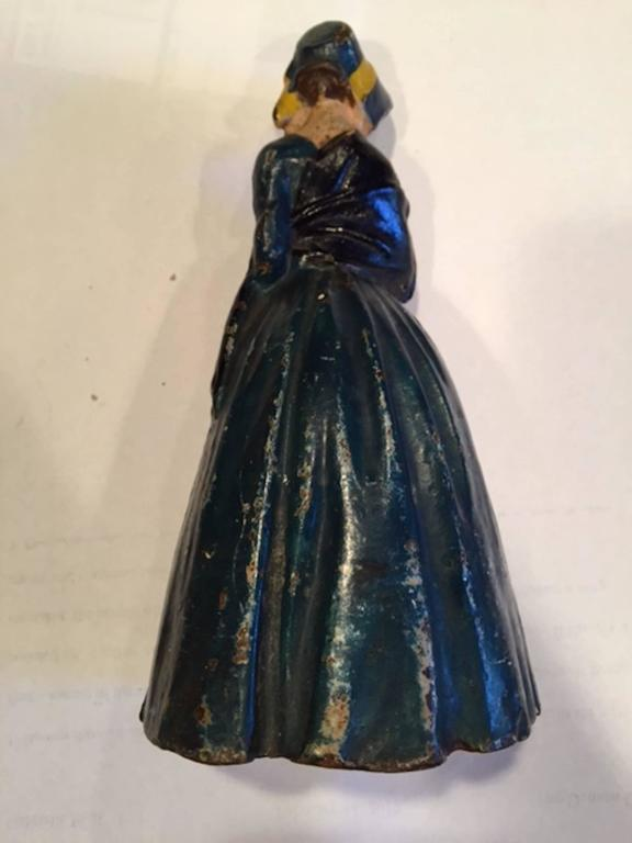 Early 20th century antique cast iron woman holding a bouquet door stop.