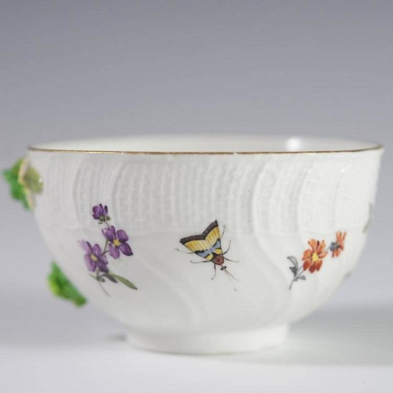 An antique Meissen demitasse cup. Features hand-painted decoration of ants and butterflies along with floral motif. Finished with molded porcelain flowers, wicker basket textured border, and gilded trim and accents. Marked on bottom with blue