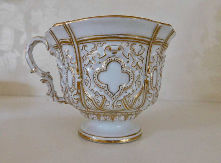 Early 20th century Meissen porcelain heavy gold trim embossed cup and saucer. White porcelain cup and saucer beautifully detailed in gold. Measurements in inches: cup 4 D x 3.13 H saucer 6 D x 1 H.