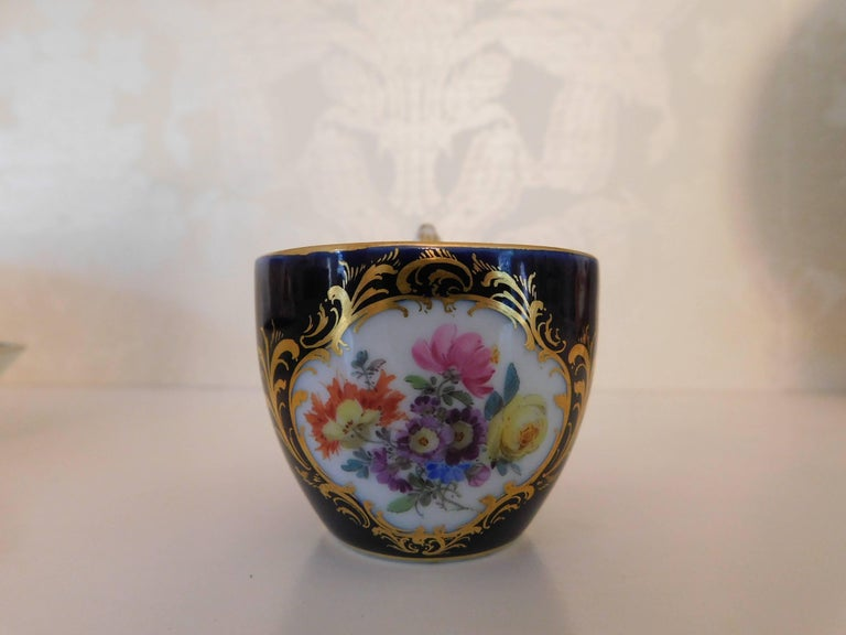 Meissen porcelain cobalt blue and floral cup and saucer.  Measurement in inches: Cup 2 D x 1.75 H Saucer 4.5 D x 1 H.
