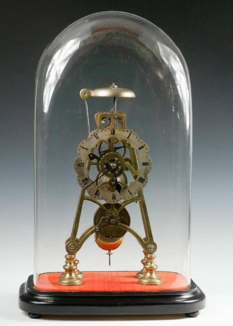 Early Skeleton clock under glass dome, with single train fusee movement, silvered dial, with striking alarm, key and pendulum, brass works and frame, set on ebonized molded wood base. Clock dimensions: 12 1/2in. high, dome: 19in. high, 11in. x 7