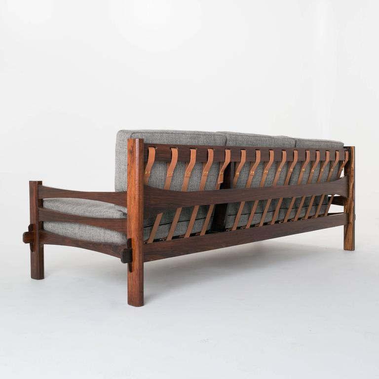 Simple Brazilian rosewood sofa. The decking in the sofa has been done in leather straps. The sap grain from the rosewood is exquisite.   In order to preserve our inventory, after restoration we blanket wrap and store nearly every piece in our