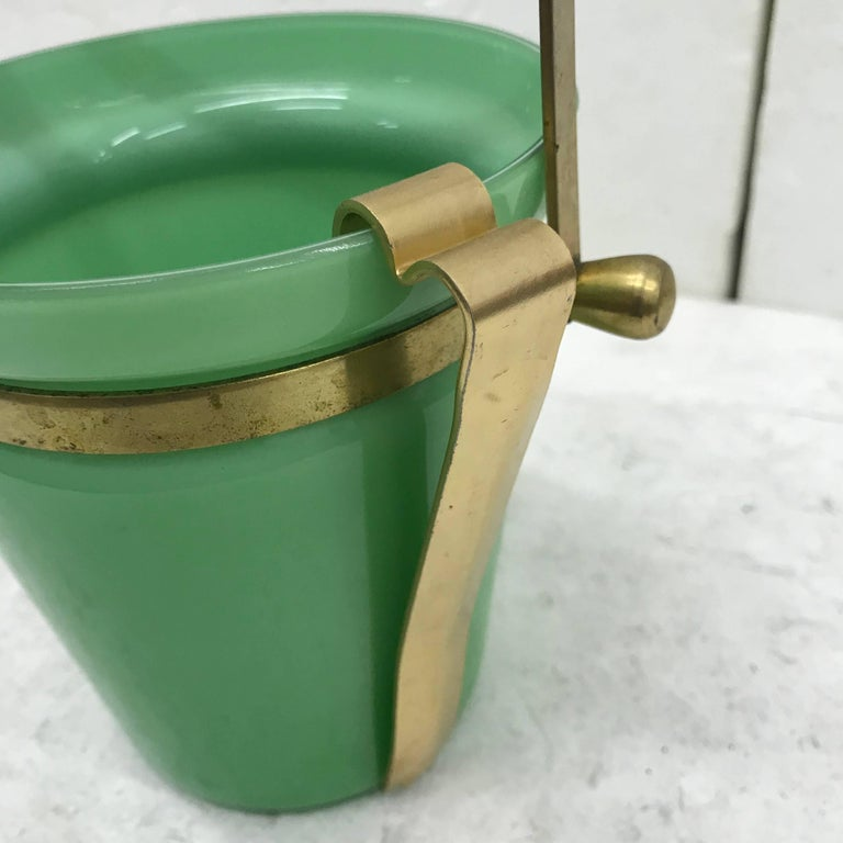 This is a brass and green opaline ice bucket made in Italy in circa 1950.