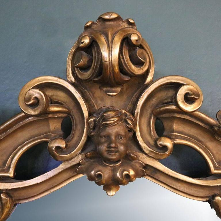 Oversized antique French overmantel pediment mirror features traditional Louis XIV style ornate giltwood surround of floral, scroll and foliate decoration with central mask on pediment crest, circa 1890  ***DELIVERY NOTICE – Due to COVID-19 we are