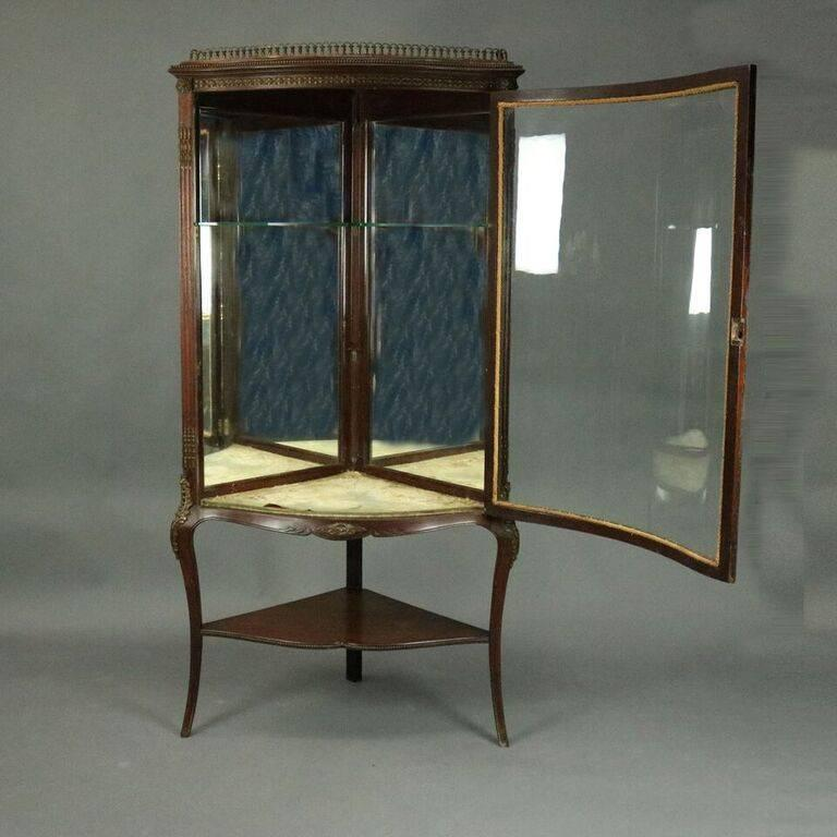 Antique French Louis XIV style R.J. Horner Brothers, NY corner china cabinet features mahogany construction with bowed front glass door opening to reveal mirrored back interior display, cabriole legs, lower shelf, bronze gallery and beaded and