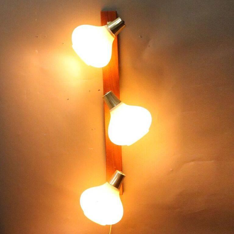 """Mid Century Danish Modern wall sconce features teak base with three teardrop-shaped molded ribbed plastic shades, circa 1960  Measures - 13""""h x 31""""w x 3""""d  *Companion wall light listed separately*"""