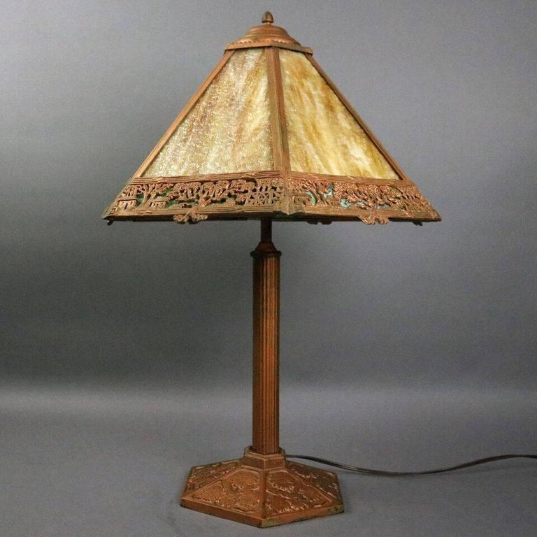 Antique Arts and Crafts Miller Co. Dual light table lamp features six-panel shade with slag glass housed in filigree shade, caramel glass over green border with countryside scene, base with reeded shaft and embossed floral foot, newly re-wired,
