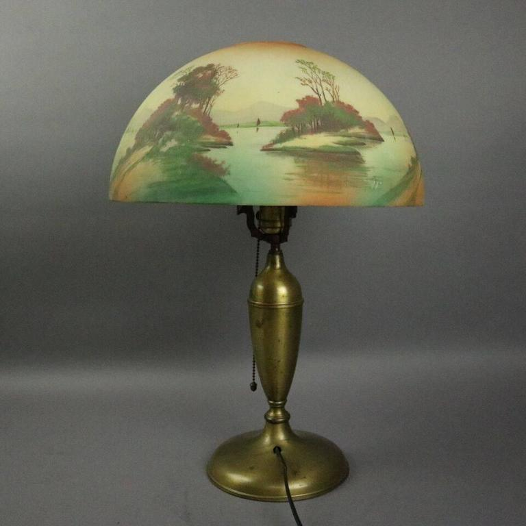Antique Pittsburgh table lamp features brass base with obverse hand painted shade depicting lake scene, circa 1920