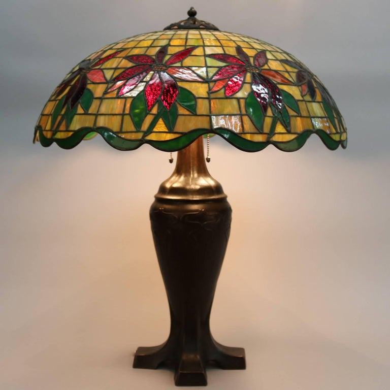 Antique handel leaded stained glass lamp features dome shade with mosaic poinsettia design, the footed standard with an Art Deco form rising to support a three-socket cluster, reminiscent of lamps by Louis Comfort Tiffany of Tiffany Studios, circa