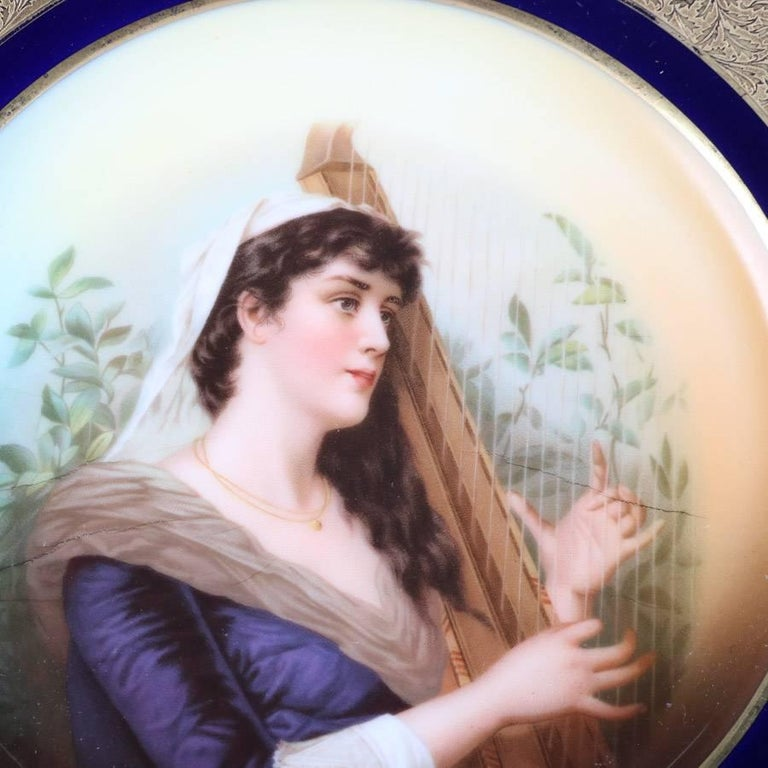 """Antique German Rosenthal porcelain plate features hand-painted portrait of princess with cobalt and gilt foliate border, en verso Rosenthal mark, 19th century  Measures: 10"""" diameter x 1.25"""" height."""
