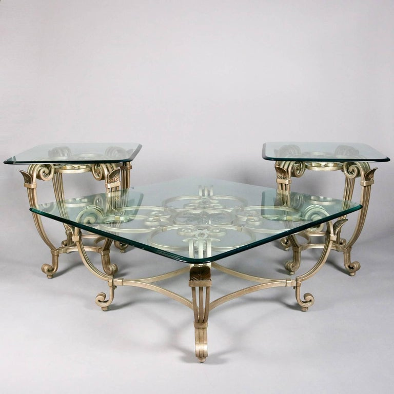 Hollywood Regency three-piece table set features scrolled and gilt iron bases with central floral and Fleur de Lis design supporting polished glass tops, includes center coffee table and two end stands, 20th century.  Measure - 20