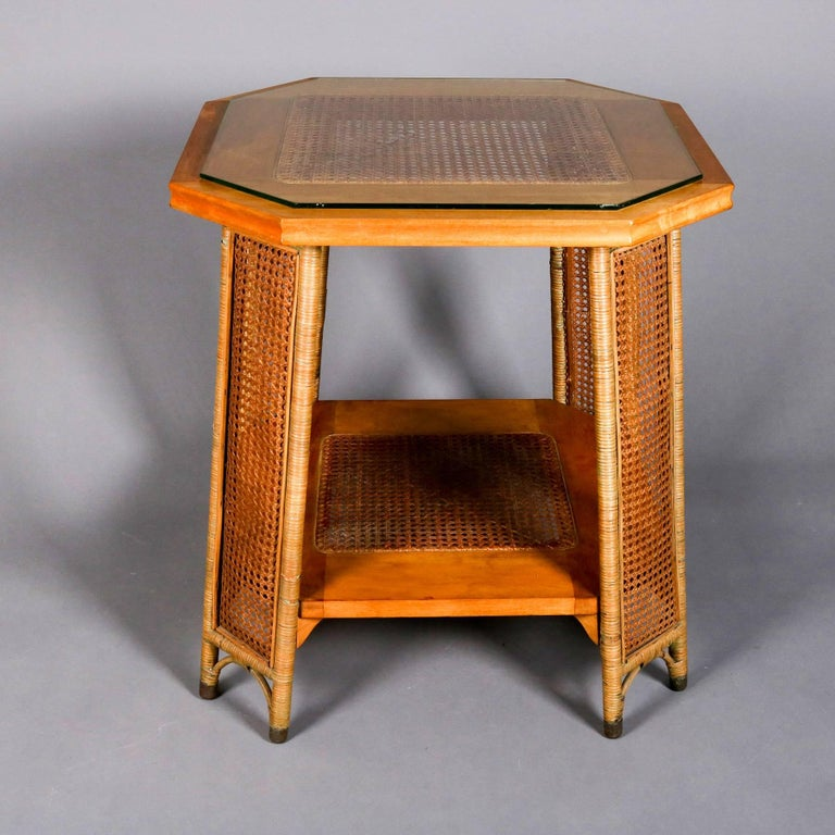 Heywood Wakefield lamp or plant stand features yew wood construction, having wicker wrapped legs with caned panels, top and lower display with caning, glass top, partial tag attached, 20th century  ***DELIVERY NOTICE – Due to COVID-19 we are
