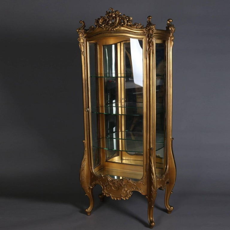 Antique French Louis XIV vitrine features giltwood case with scroll, foliate and floral decoration, pierced crest with cartouche, seated on exaggerated cabriole legs, single bow front glass door opens to mirror back interior display with glass