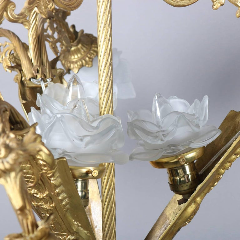 Vintage French Louis XIV style chandelier features gilt foliate form frame, nine arms terminating in lights with frosted molded floral form shades, newly re-wired, 20th century  ***DELIVERY NOTICE – Due to COVID-19 we are employing NO-CONTACT