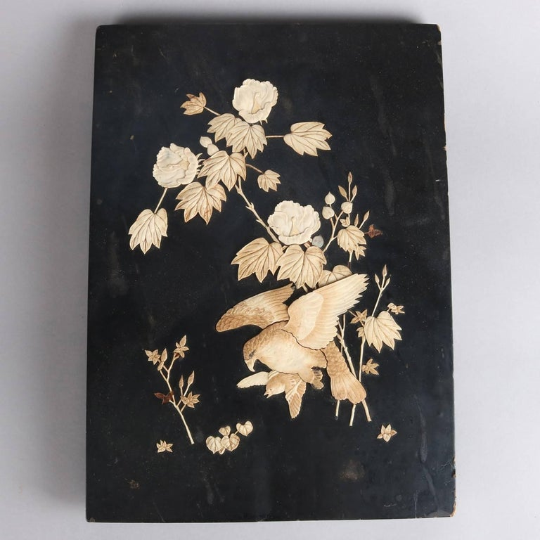 Antique Japanese plaque features ebonized wood base with bone inlay depicting hunt scene with falcon and sparrow in flowering bush, 20th century  Measures: 14.5