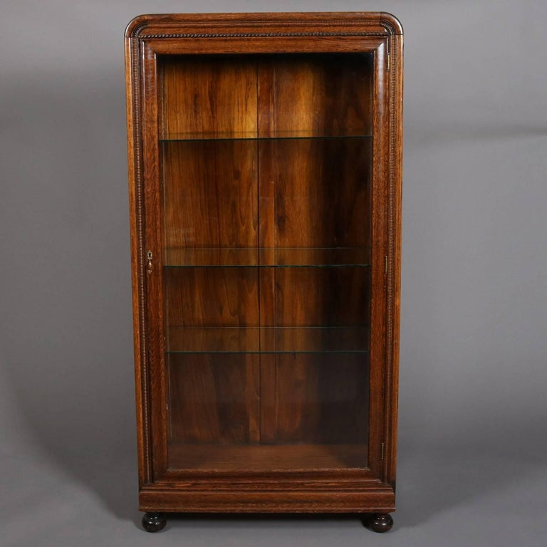 Antique oak display cabinet features single door opening to glass shelved  interior and seated on ball - Antique Oak Single Glass Door Closed Display Cabinet, Ball Feet