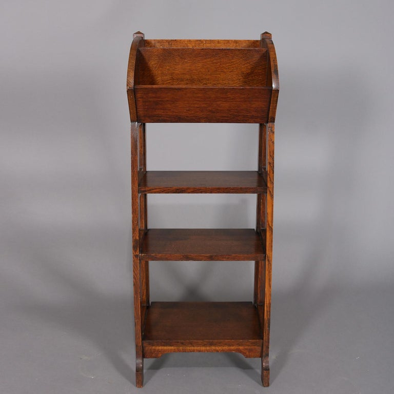 Antique Arts & Crafts Stickley School oak magazine rack features upper divided tray above three graduated lower shelves with open sides, circa 1910  Measures: 40