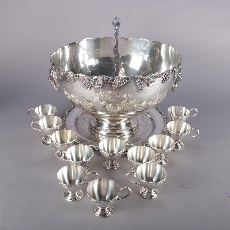 Antique Victorian silver plate punch bowl set features bowl with scalloped rim having high relief grape and leaf decoration with two lion mask handles and raised on column base with underplate, set with 12 grape and leaf pedestal cups and ladle, en