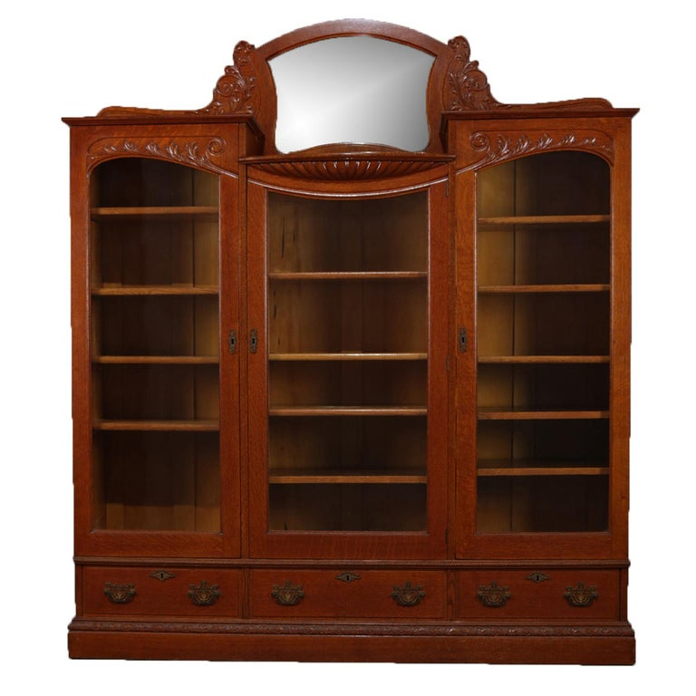 Antique Horner school bookcase features crest with central mirror and  flanking carved foliate frame above three - Antique Horner School Carved Golden Oak Three-Door Mirrored Bookcase