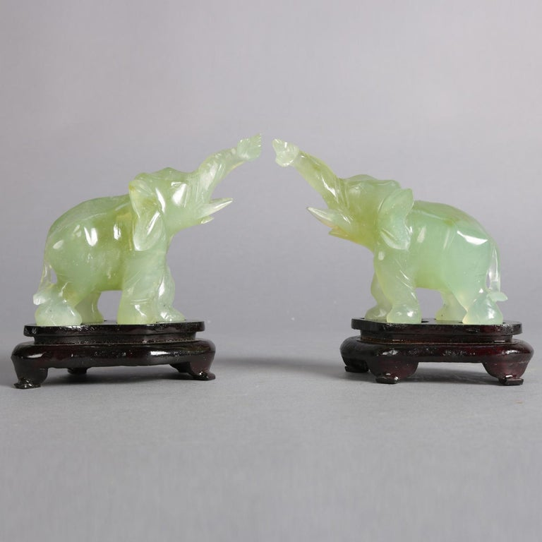 Pair of Asian carved jade elephant sculptures with upswept trunks symbolizing