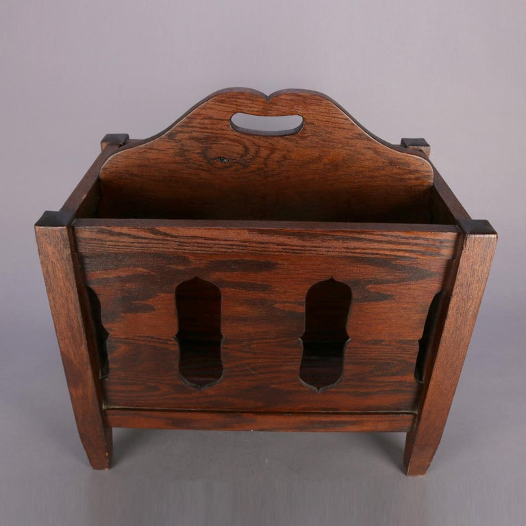 Arts & Crafts Stickley School mission oak magazine rack features quarter sawn oak construction with cut-out sides and central divider with handle, raised on square and slightly tapered legs, circa 1910.  Measures: 20