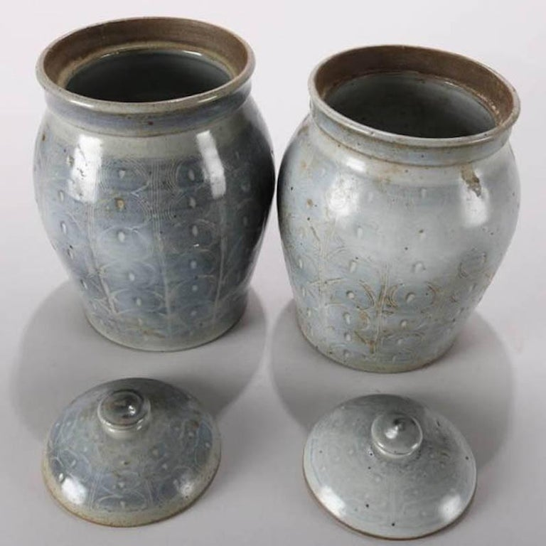 """Pair of Mid-Century Modern hand-thrown studio art pottery lidded jars or canisters feature milky blue glaze over incised repeating design of linear pattern concentric circles, singed """"H"""" on base, mid-20th century Provenance: Deaccessioned"""