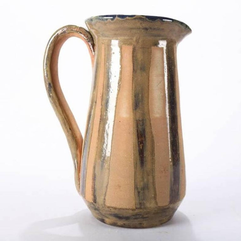 Mid-Century Modern hand-thrown studio art pottery pitcher features striped exterior with cobalt blue glazed interior, mid 20th century Provenance: Deaccessioned from the Call Museum, Hartsville, New York  ***DELIVERY NOTICE – Due to COVID-19 we are