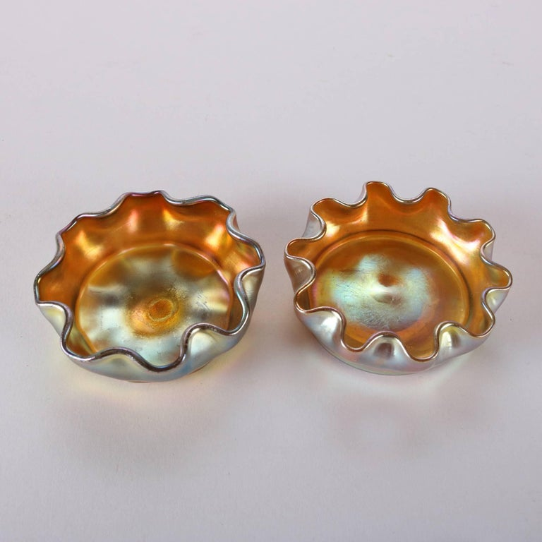 Pair of antique gold Favrile art glass salt cellars by Louis Comfort Tiffany feature with iridized exterior finish and ruffled rims, signed on bases L.C.T., 19th century  Measure: 1