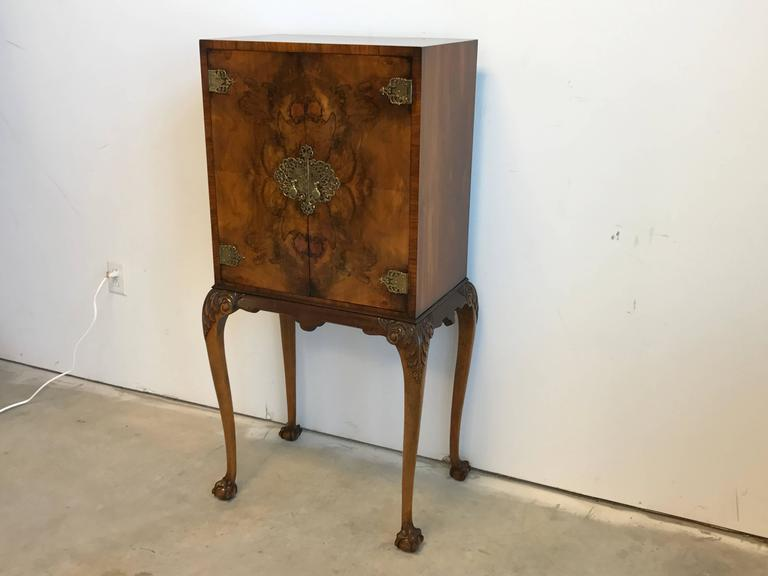Offered is an absolutely stunning, 19th century maple-burl wood bar cabinet. This piece is a showstopper with its gorgeous and ornate brass detailing and claw feet detailing. Inside has an upper rack for glasses, beneath is a glass and wood serving