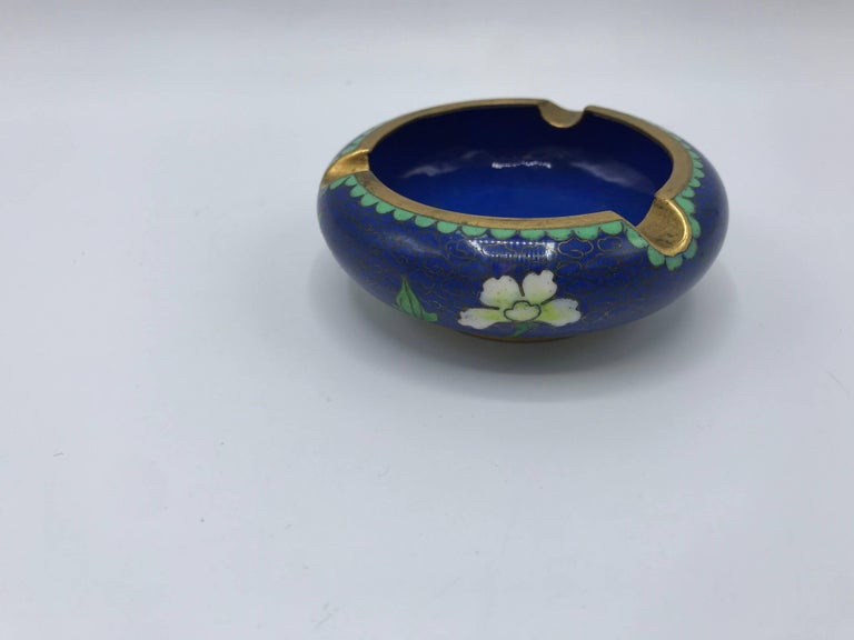 Offered is a gorgeous, small 1960s blue cloisonné ashtray with a thick brass lip. Looks like it has never been used.