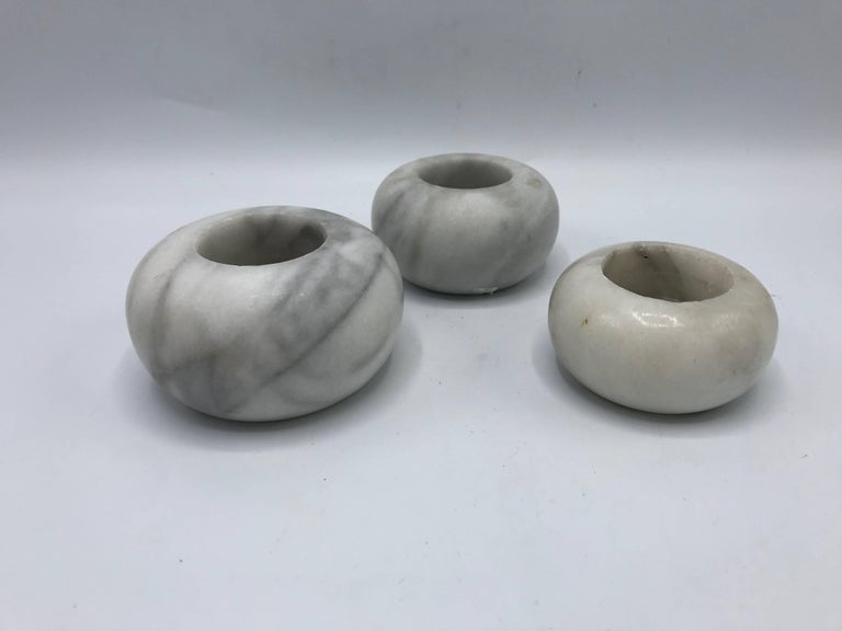 """Offered is a fabulous, set of three, 1960s Italian white marble votive candleholders. Set of three descend in size. Heavy. Measures: Large 3.75"""" x 2"""" Medium 3.5"""" x 1.75"""" Small 3"""" x 1.5""""."""