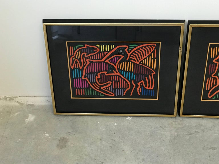 Offered is a stunning, pair of 1970s Guatemalan Mola textile panels framed. One features a fish and bird motif, the other is a fish and mammal motif. Each are framed in a thick black and gold frame, behind glass.   Molas are handmade using a reverse