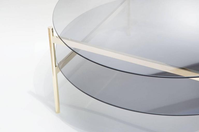Made to order. Please allow 6 weeks for production.  Brass Frame / Smoked Glass / Smoked Glass  The Duotone Furniture series is based on a modular hardware system that pairs sturdy construction with visual lightness and a range of potential