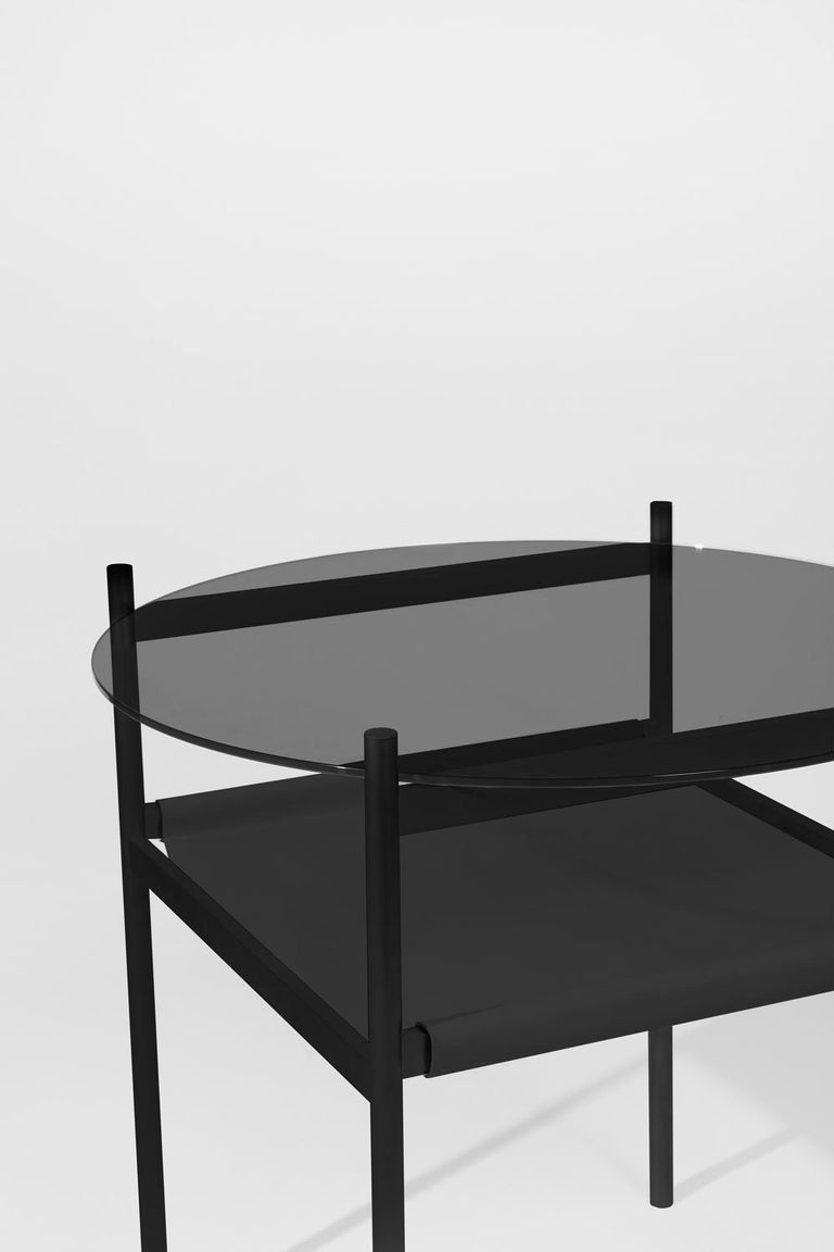 Made to order. Please allow 6 weeks for production.  Black frame / Smoked glass / Black leather sling.  The Duotone Furniture series is based on a modular hardware system that pairs sturdy construction with visual lightness and a range of