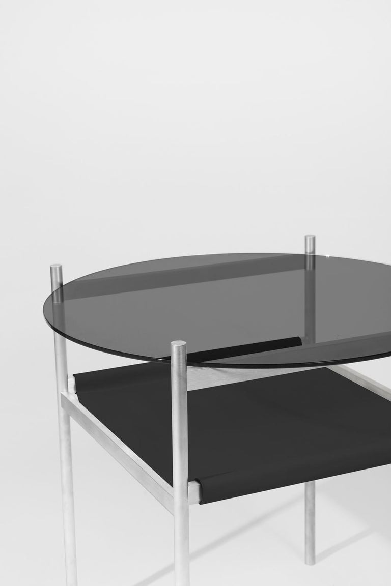 Made to order. Please allow 6 weeks for production.  Aluminium frame / Smoked glass / Black leather sling.  The Duotone Furniture series is based on a modular hardware system that pairs sturdy construction with visual lightness and a range of