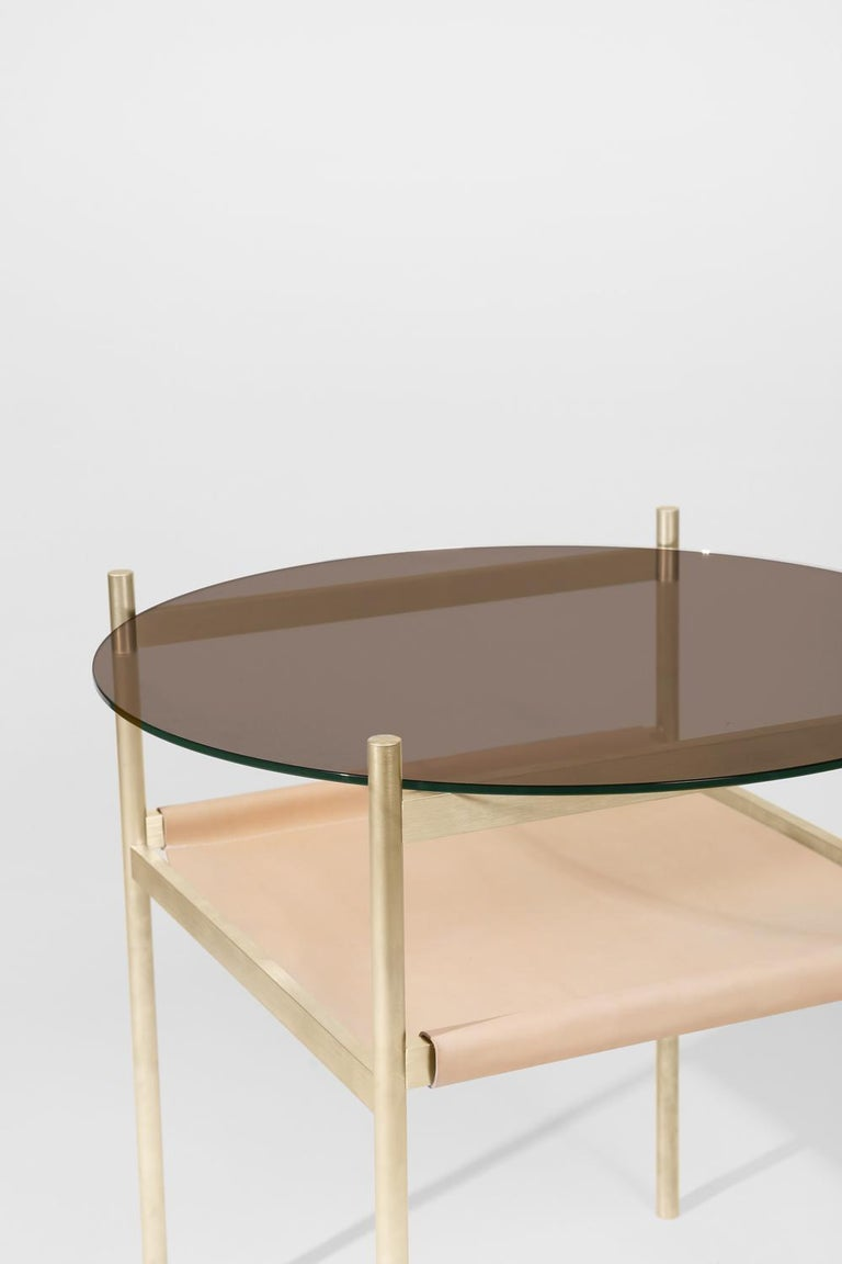 Made to order. Please allow six weeks for production.  Brass Frame / Bronze Glass / Natural Leather Sling  The Duotone Furniture series is based on a modular hardware system that pairs sturdy construction with visual lightness and a range of