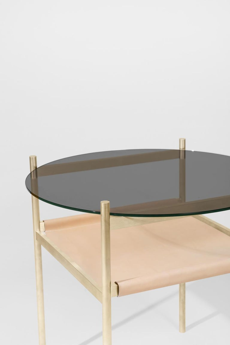 Made to order. Please allow six weeks for production.  Brass frame / smoked glass / natural leather sling  The Duotone furniture series is based on a modular hardware system that pairs sturdy construction with visual lightness and a range of