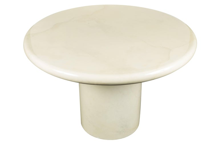 Round, sculptural, center or dining table by Karl Springer. Clad in Ivory colored goatskin, with high gloss lacquer finish.