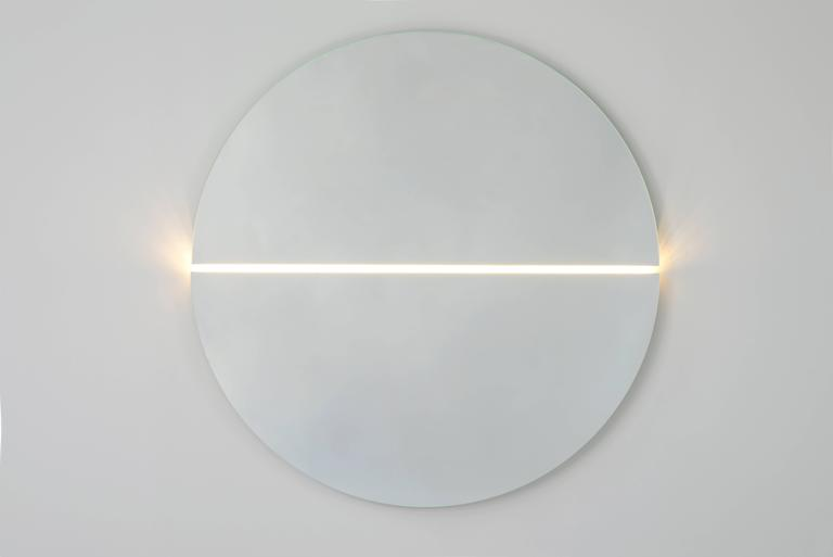 Two large half circle panels of glass are cut through the centre by the glow of light, accenting the negative space and playing with subtleties of light and shadow.  Order details: Made to order, custom sizing and colors available upon