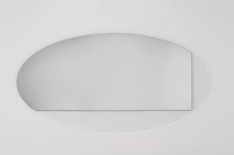 The Iris is a large-scale oval mirror that partners mirror with translucent glass, creating unexpected layers of light and reflection.   Order details: Made to order, custom sizing and colors available upon request.  Shipping: The Iris mirror ships