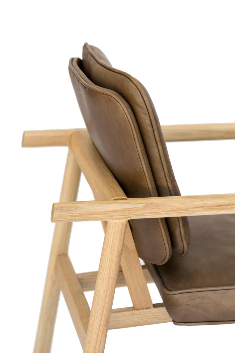 Solid wood construction with hand-cut joinery and custom upholstered seat and seat back. This chair shown in natural oak and olive leather.  In stock leather choice: black, olive, camel or vegan leather. Wood choice: ebonized oak, walnut, natural